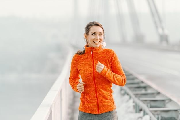 Mulher caucasiana feliz no sportswear e com rabo de cavalo correndo na ponte no inverno. conceito de aptidão de inverno.