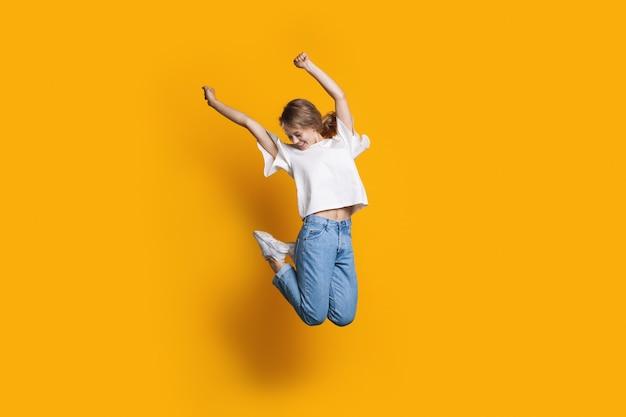 Mulher caucasiana feliz pulando na parede amarela de um estúdio gesticulando felicidade