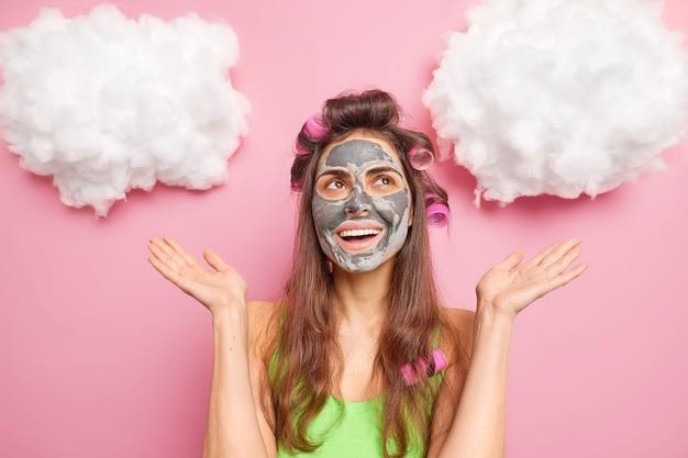 Mulher caucasiana feliz satisfeita aplica máscara de beleza no rosto espalha as palmas das mãos e olha feliz acima se prepara para o encontro quer ter look fabuloso isolado sobre parede rosa