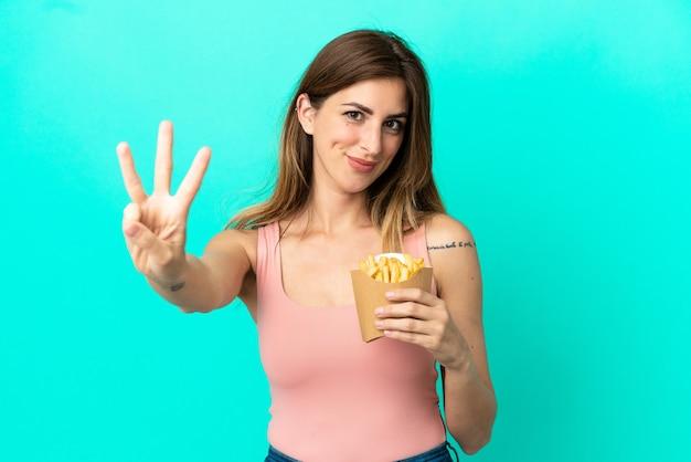 Mulher caucasiana feliz segurando batatas fritas isoladas em um fundo azul e contando três com os dedos
