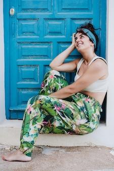 Mulher caucasiana feliz sentada em frente a uma porta azul durante o verão. sonhando acordado. estilo de vida ao ar livre