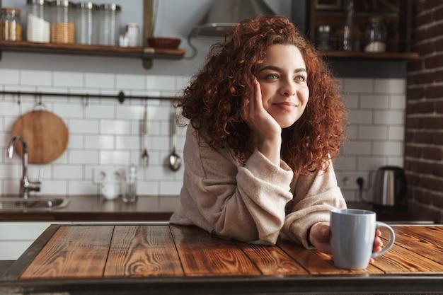 Mulher caucasiana feliz sorrindo e bebendo chá ou café enquanto toma o café da manhã no interior da cozinha em casa