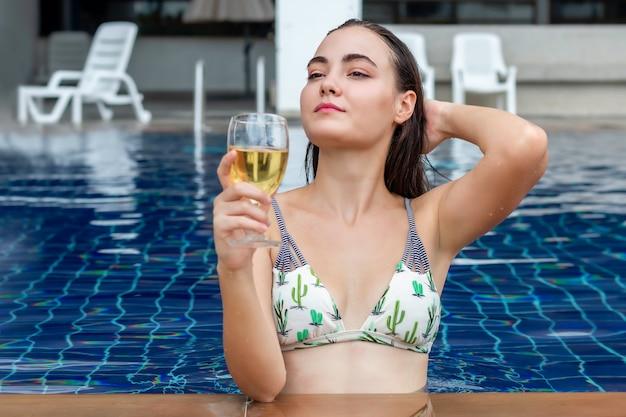 Mulher caucasiana feliz vestindo um biquíni segurando e bebendo um cocktail perto da piscina.