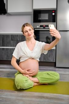 Mulher caucasiana fofa tira foto no celular depois de fazer exercícios de ioga durante a gravidez