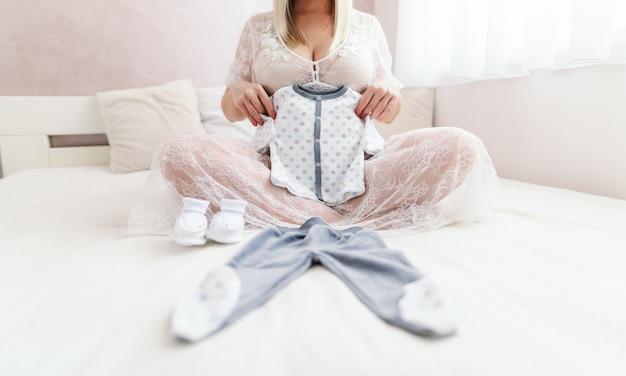 Mulher caucasiana grávida segurando as roupas do bebê wile sentado na cama com as pernas cruzadas no quarto.