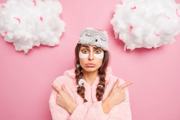 Mulher caucasiana hesitante e sem noção aponta para lados diferentes, tem expressão surpresa se sente confusa escolhe entre dois itens vestida de pijama após acordar isolada sobre a parede rosa
