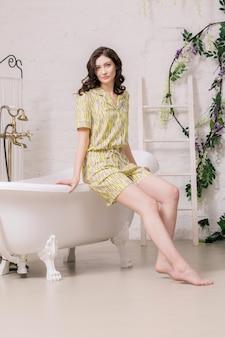 Mulher caucasiana incrível em um macacão amarelo, posando em um banheiro.