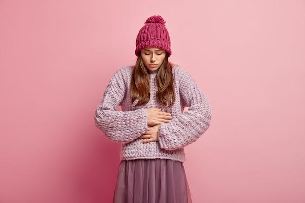 Mulher caucasiana infeliz mantém as duas mãos na barriga, come comida estragada, tem uma sensação desagradável no estômago, usa capacete rosa com pompon, suéter de malha e saia plissada, fica de pé sobre parede rosa