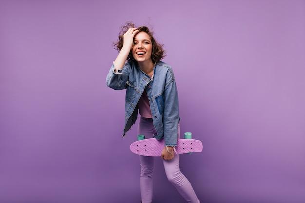 Mulher caucasiana inspirada em traje casual, expressando boas emoções. garota encaracolada despreocupada com pé de skate.