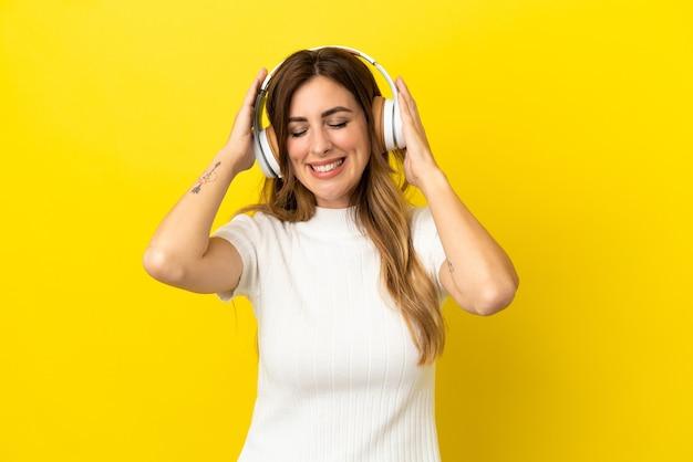 Mulher caucasiana isolada em fundo amarelo ouvindo música