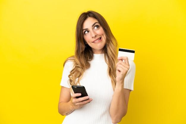 Mulher caucasiana isolada em um fundo amarelo comprando com o celular com um cartão de crédito enquanto pensa