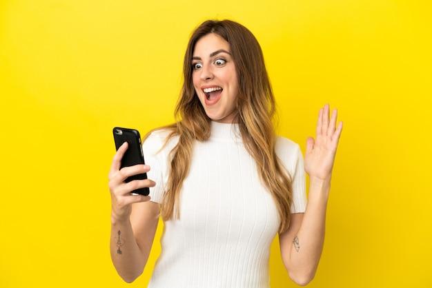 Mulher caucasiana isolada em um fundo amarelo olhando para a câmera enquanto usa o celular com expressão de surpresa