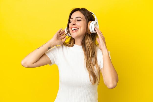 Mulher caucasiana isolada em um fundo amarelo ouvindo música e cantando