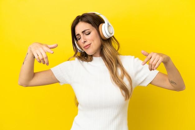 Mulher caucasiana isolada em um fundo amarelo ouvindo música e dançando
