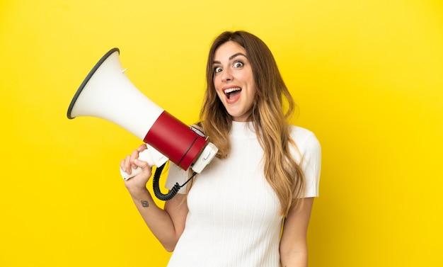 Mulher caucasiana isolada em um fundo amarelo segurando um megafone e com expressão de surpresa