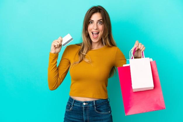 Mulher caucasiana isolada em um fundo azul segurando sacolas de compras e surpresa