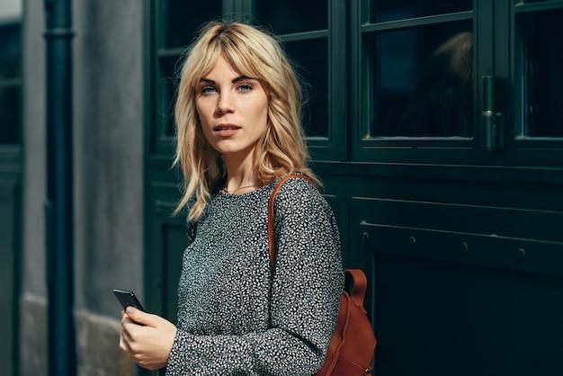 Mulher caucasiana jovem atraente olhando para o seu telefone inteligente ao ar livre