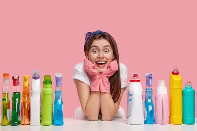 Mulher caucasiana jovem e feliz segura o queixo, usa luvas de proteção de borracha e bandana e sorri amplamente