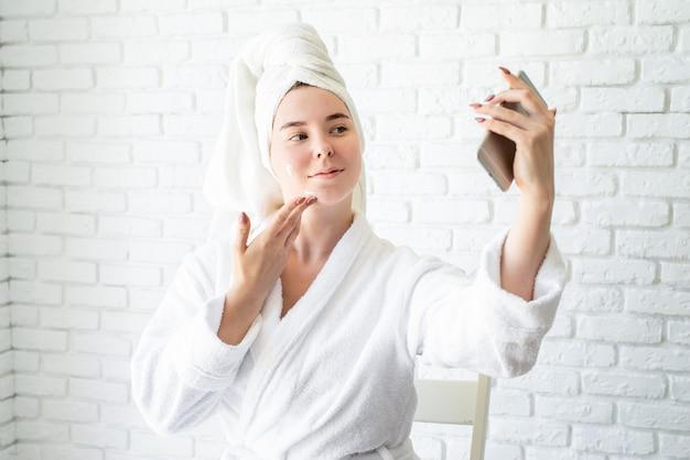 Mulher caucasiana jovem feliz em toalha de banho branca, aplicando creme facial em casa fazendo selfie