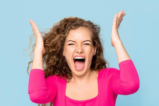 Mulher caucasiana jovem irritada chocada gritando isolado na parede azul clara
