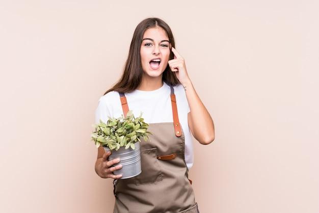 Mulher caucasiana jovem jardineiro segurando uma planta isolatedshowing um gesto de decepção com o dedo indicador.