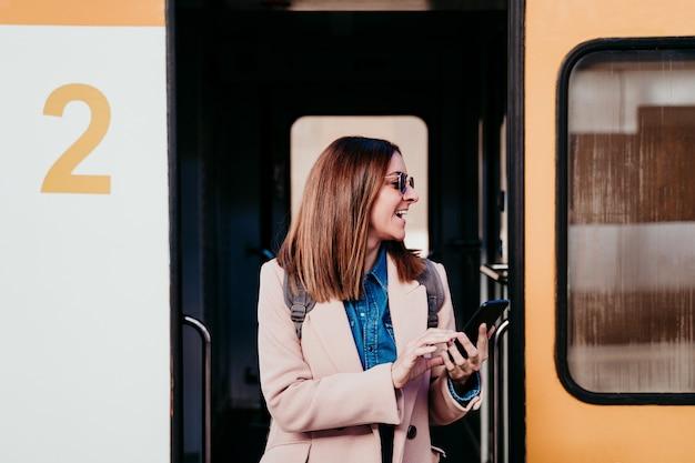 Mulher caucasiana jovem mochileiro na estação de trem usando telefone celular. conceito de viagens