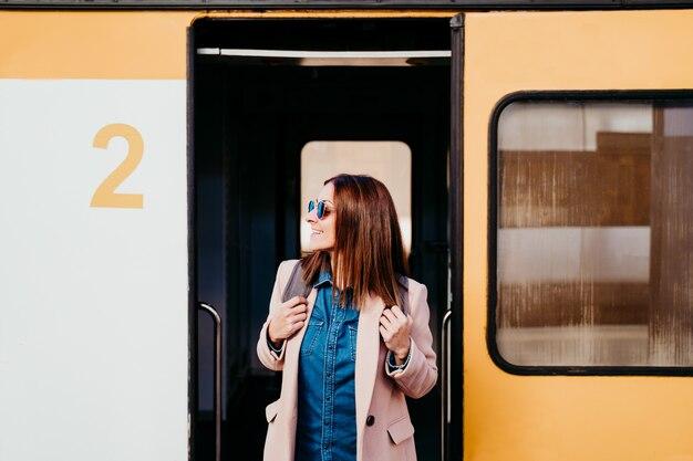 Mulher caucasiana jovem mochileiro sorridente em pé na carroça na estação de trem. conceito de viagens
