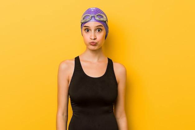 Mulher caucasiana jovem nadador sopra bochechas, tem expressão cansada.