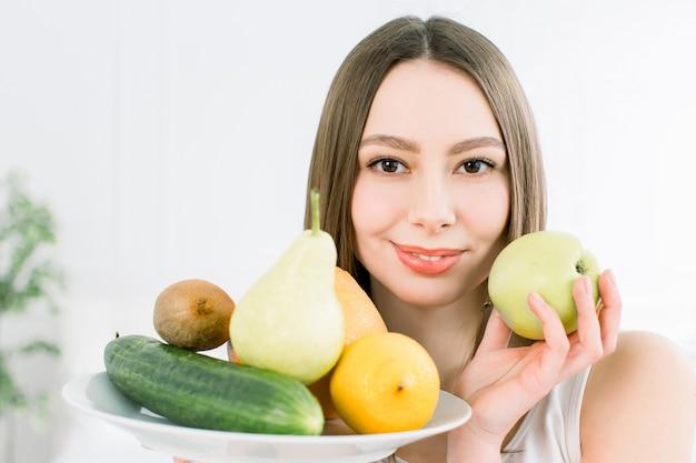 Mulher caucasiana jovem sorridente atraente segurando um prato com legumes amarelos verdes e frutas sobre o fundo claro. saudável, beleza, boa comida produtos vegetarianos.