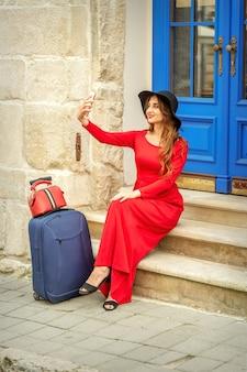 Mulher caucasiana jovem turista em um vestido longo vermelho e chapéu preto com mala leva uma selfie sentado.
