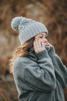Mulher caucasiana jovem vestindo um suéter cinza e um chapéu de inverno - conceito de inverno