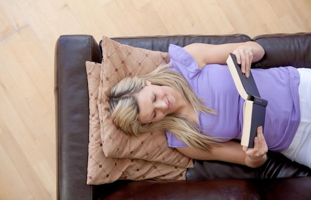 Mulher caucasiana, lendo um livro em um sofá
