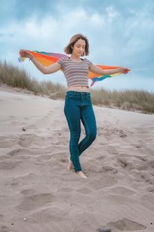 Mulher caucasiana lésbica na praia segurando o arco-íris bandeira orgulho - imagem stock