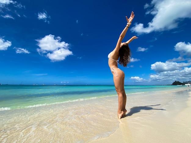 Mulher caucasiana linda sexy posando de biquíni branco na costa do mar