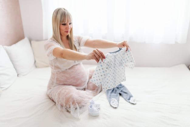 Mulher caucasiana loira sorridente bonita segurando e olhando as roupas do bebê enquanto está sentado na cama com as pernas cruzadas. interior do quarto.