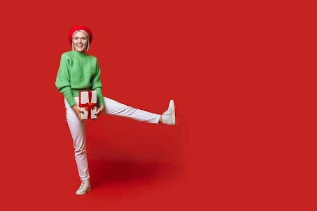 Mulher caucasiana, loira, usando um chapéu, posando com um presente na parede vermelha de um estúdio com um espaço livre anunciando algo