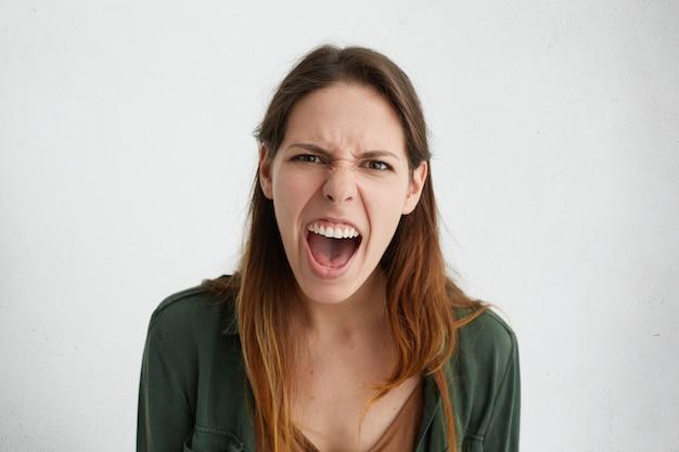 Mulher caucasiana louca gritando alto, abrindo o rosto carrancudo de boca com raiva, demonstrando suas emoções negativas.