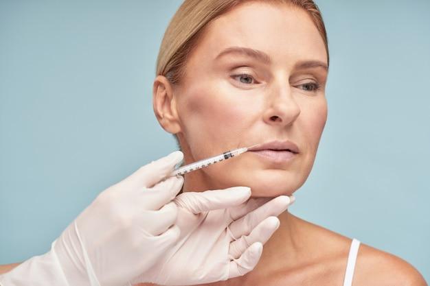 Mulher caucasiana madura e atraente fazendo procedimento de aumento de lábios por cosmetologista em pé