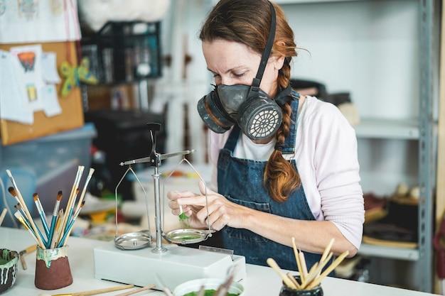 Mulher caucasiana misturando cores de pintura com um equilíbrio vintage dentro de seu estúdio de cerâmica criativa - foco no olho dela