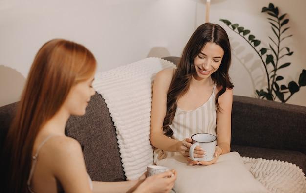 Mulher caucasiana morena está tendo uma discussão interessante com o amigo gengibre enquanto bebe uma xícara de chá e está sentada no sofá