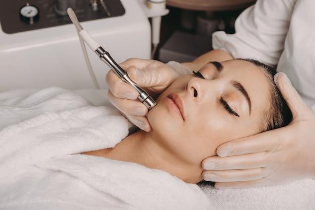 Mulher caucasiana morena fazendo um procedimento de spa para a pele do rosto realizado com um aparelho por um funcionário do spa