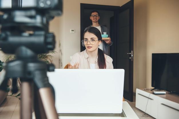 Mulher caucasiana morena tendo uma aula online esperando o marido trazer o café da manhã para ela