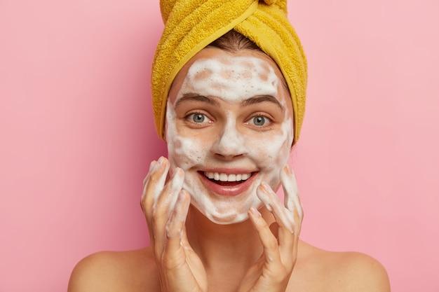Mulher caucasiana muito sorridente mima o rosto, lava a pele com espuma de gel, usa uma toalha amarela enrolada na cabeça, se preocupa com o corpo
