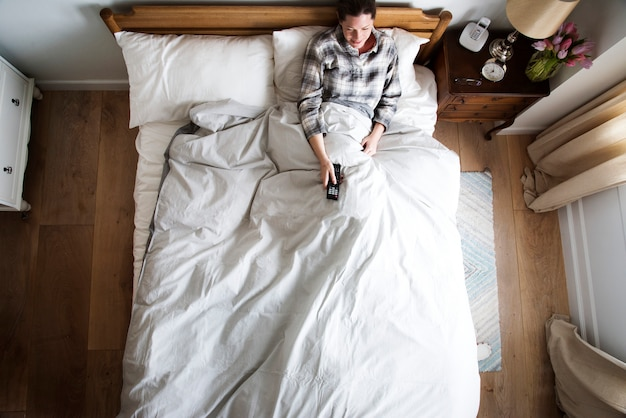 Mulher caucasiana na cama assistindo tv