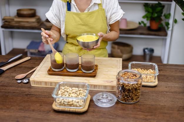 Mulher caucasiana na cozinha faz pudins de chia com geleia de manga. deserto feito de leite de amêndoa, sementes de chia, cacau, geléia de manga e granola.