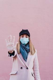 Mulher caucasiana na rua usando máscara protetora e fazendo um sinal de stop com a mão. conceito de vírus corona