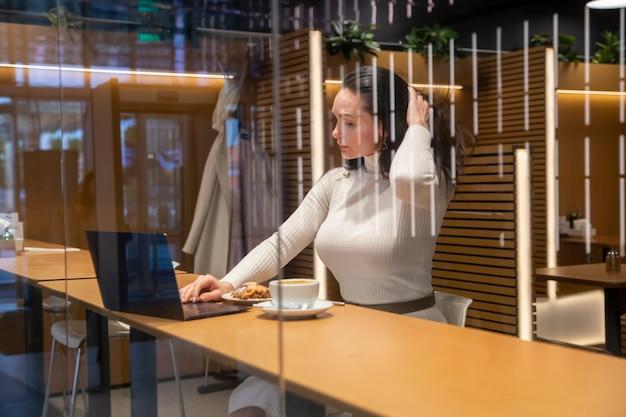 Mulher caucasiana no café, trabalhando no laptop e bebendo café.