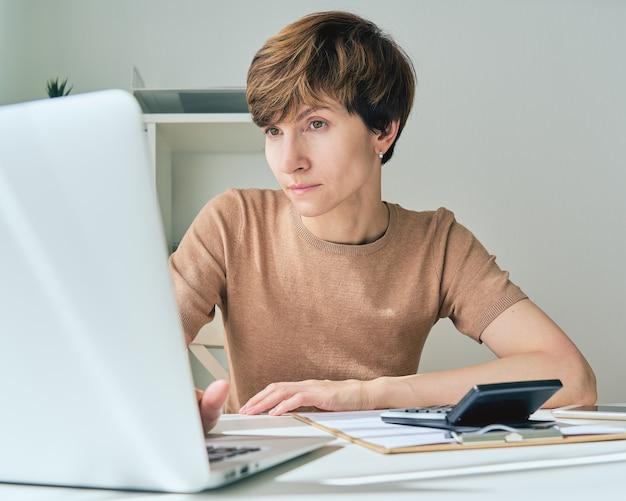 Mulher caucasiana olhando para um laptop e calculando as despesas, mantendo registros financeiros