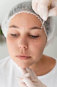 Mulher caucasiana passando por procedimento de microblading