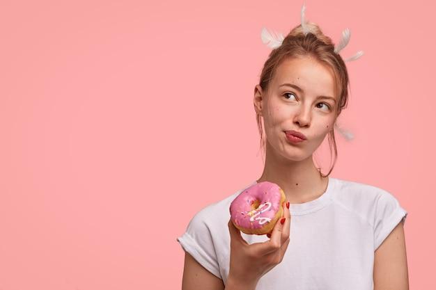 Mulher caucasiana pensativa com penas na cabeça, olhando pensativamente de lado, segurando um delicioso donut doce, vestida com uma camiseta branca casual, encostada na parede rosa com espaço em branco para texto